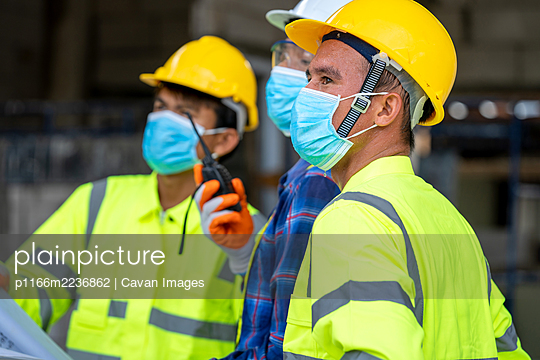 Group civil engineer wearing protective face mask during the ins - p1166m2236862 by Cavan Images