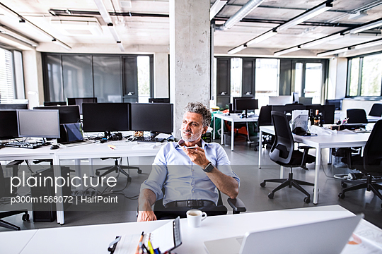 Mature businessman sitting at desk in office using smartphone - p300m1568072 by HalfPoint