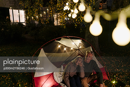 Senior couple camping in garden of their home at night - p300m2156246 by Gustafsson