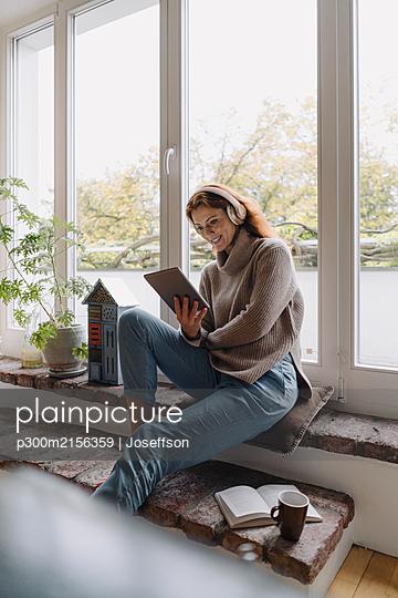 Mature woman sitting on wondow sill, using digital tablet - p300m2156359 by Joseffson