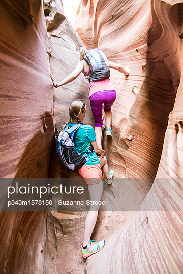 Two women canyoneering through narrow Zebra Canyon, Grand Staircase-Escalante National Monument, Utah, USA - p343m1578150 by Suzanne Stroeer