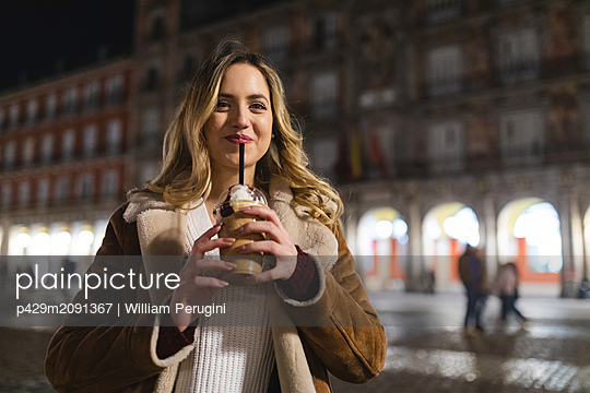 Young woman with long blond hair drinking frappe coffee on city street at night, Madrid, Spain - p429m2091367 by William Perugini