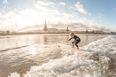Cute toddler surfing on a wave at a beach in New Zealand - p1166m2108130 by Cavan Images