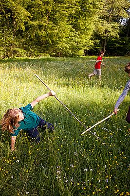 Kinder spielen und kämpfen im Park - p1195m1138138 von Kathrin Brunnhofer