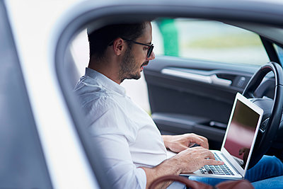 Businessman sitting in car working on laptop - p300m2012208 by gpointstudio