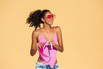 Portrait of teenage girl wearing sunglasses, orange wall - p300m2069583 von Eloisa Ramos