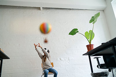 Girl with VR glasses trying to catch hot-air balloon in office - p300m2156103 by Gustafsson