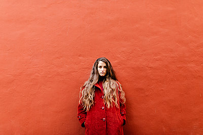 Portrait of selfconfident young woman with long brown hair wearing red jacket leaning against red wall - p300m2160393 von Tania Cervián