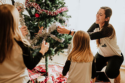 Cheerful parents with daughters decorating Christmas tree at home - p300m2251599 by Gala Martínez López