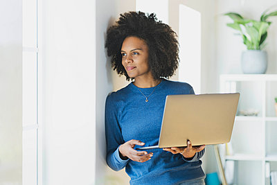 Young woman holding laptop while leaning on wall at home - p300m2276426 by Steve Brookland