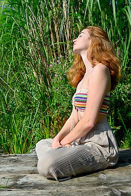 Junge Frau macht Yoga am See - p427m2209792 von Ralf Mohr