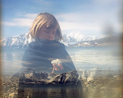 Girl holding stone with fjord in background - p945m1468049 by aurelia frey