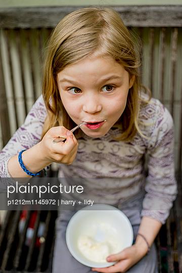 Mädchen isst Eis im Garten - p1212m1145972 von harry + lidy