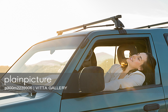 Relaxed young woman leaning on car window during road trip - p300m2239906 by VITTA GALLERY