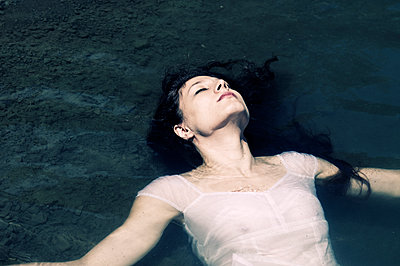 Young woman floating in water - p1445m2128448 by Eugenia Kyriakopoulou
