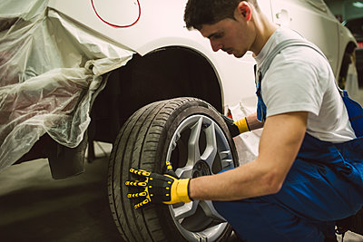 Mechanic changing car tyre in his workshop - p300m1587809 by Ramon Espelt