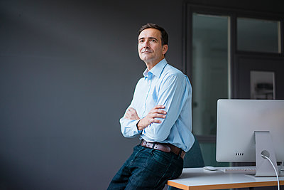 Confident businessman leaning against desk in the office - p300m2070022 von Joseffson