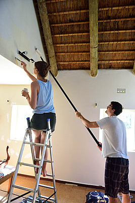 Young couple renovating their home painting the wall together - p300m2079225 by Eyecatcher.pro
