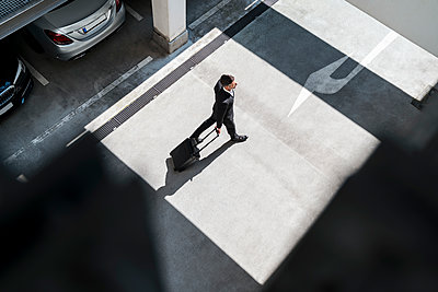 Top view of businessman with baggage on the go - p300m2139805 von Daniel Ingold