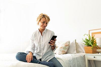 Mature woman sitting on bed at home using smartphone - p300m2144788 by Valentina Barreto