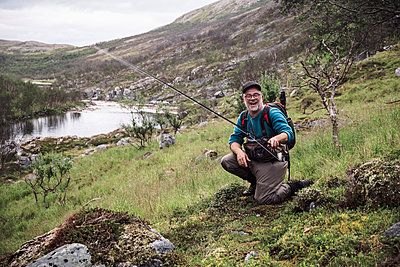 Laughing fly fisherman at river bank with mountains, Lakselv, Norway - p300m2166817 by Studio 27