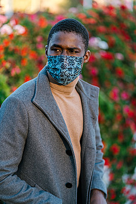 Man wearing face mask looking away while standing at park - p300m2251043 by Ezequiel Giménez