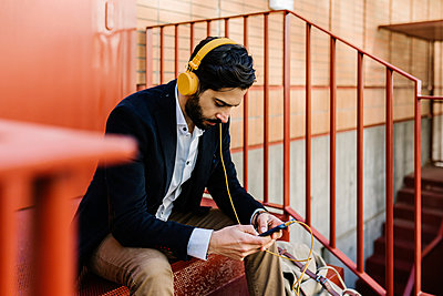 Businessman wearing headphones using mobile phone while sitting on steps - p300m2256893 by Xavier Lorenzo