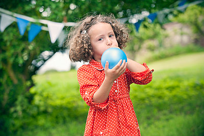 Girl blowing up balloon outdoors - p429m746867f by Colin Hawkins