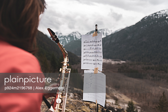 Woman standing on a mountain in the Squamish Valley, British Columbia, Canada, playing the saxophone. - p924m2196768 by Alex Eggermont