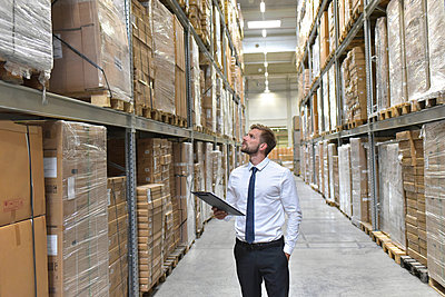 Businessman with clipboard in warehouse looking at shelves - p300m1499245 by lyzs
