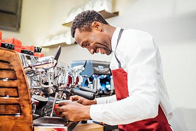 Smiling barista preparing a coffee in a coffee shop - p300m2167411 von Oscar Carrascosa Martinez