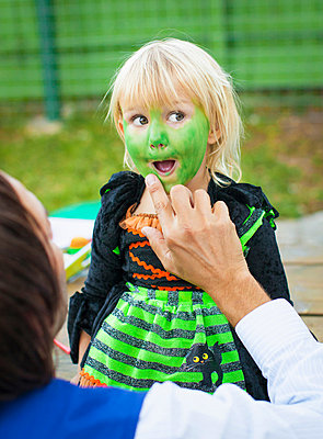 Man painting child's face green - p429m819584 by Angela Bird