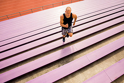 Caucasian man running on purple bleachers - p555m1304605 by Adam Hester