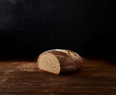 Brotlaib angeschnitten auf Holzplatte - p897m1541150 von MICK