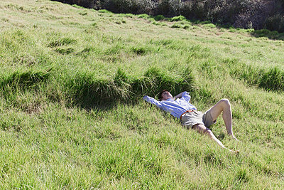 Man laying on field - p956m1044254 by Anna Quinn