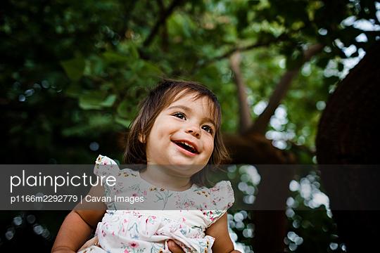 One Year Old Sitting in Tree & Smiling in San Diego - p1166m2292779 by Cavan Images