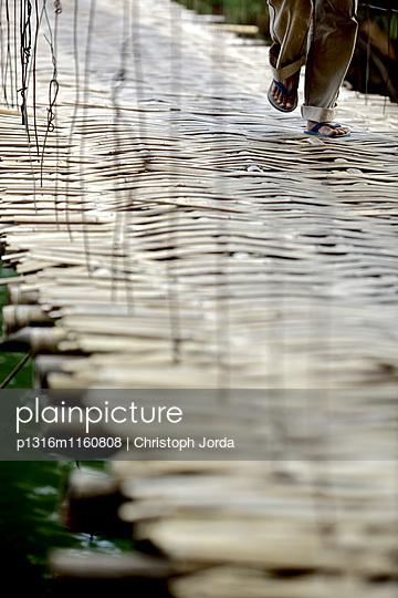 Mann läuft über eine einfache Bambusbrücke, Denpasar, Bali, Indonesien - p1316m1160808 von Christoph Jorda