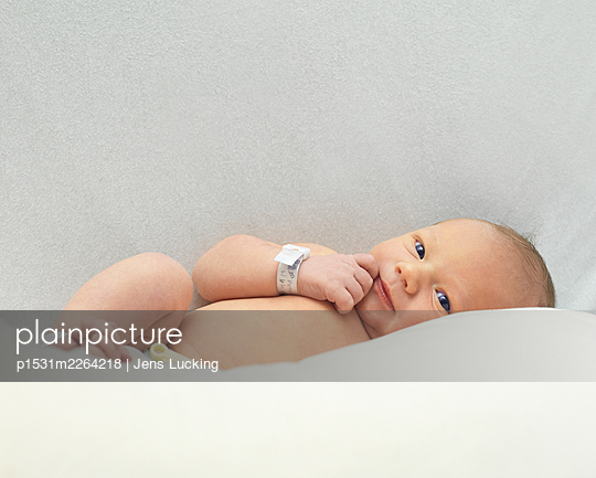 Baby boy, 1 day old, lying on bed, smiling - p1531m2264218 by Jens Lucking