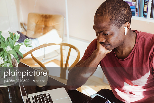 Worried male entrepreneur with hand on chin looking at laptop while working from home office - p426m2279802 by Maskot
