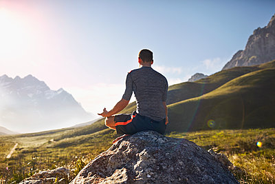 Young man meditating on rock in sunny, remote valley - p1023m1226643 by Trevor Adeline