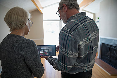 Senior couple with digital tablet using augmented reality to plan living room remodel - p1192m1559989 by Hero Images