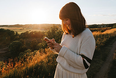Happy texting girl - p1507m2165741 by Emma Grann