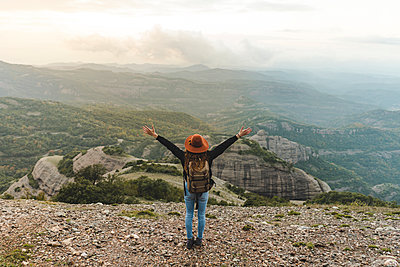 Woman with backback, standing on mountain, looking at view - p300m2079013 von VITTA GALLERY
