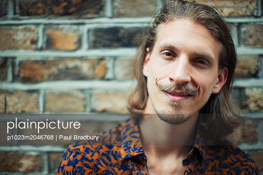 Portrait smiling, confident young male hipster with mustache - p1023m2046768 by Paul Bradbury
