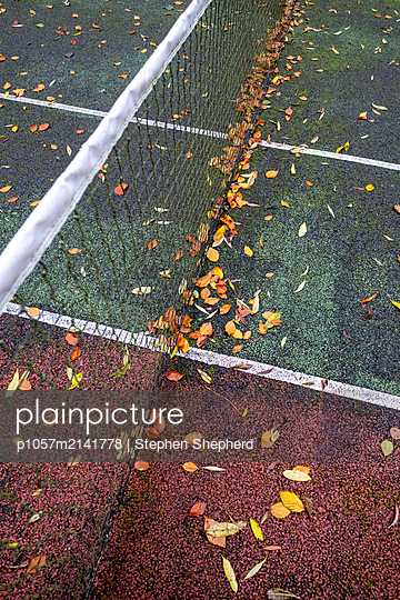 A tennis coourt covered with fallen leaves lying on the coloured surface with net and markings of white lines on the surface. - p1057m2141778 by Stephen Shepherd