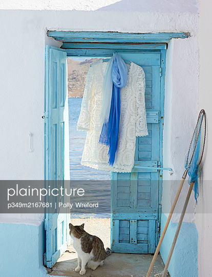 Lace dress hangs in doorway of Greek villa with fishing net and cat looking back. - p349m2167681 by Polly Wreford