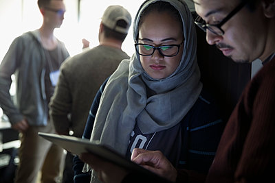 Female hacker in hijab working with teammate at hackathon using digital tablet - p1192m1202090 by Hero Images