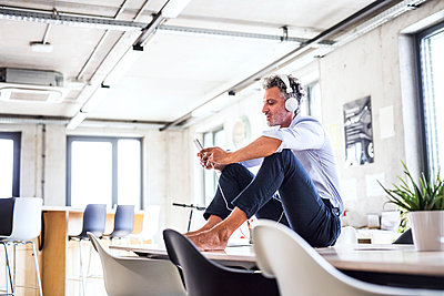 Mature businessman with smartphone and headphones sitting barefoot on desk in office - p300m1568064 von HalfPoint