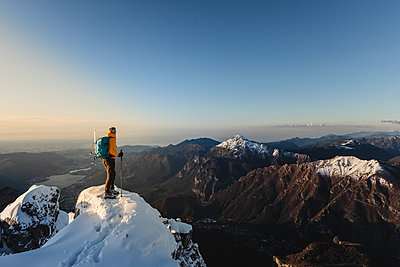 Mountaineer standing on top of a snowy mountain enjoying the view, Lecco, Italy - p300m2155577 by 27exp