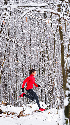 Female sportsperson running over snow covered fallen tree during winter - p300m2257293 by Stefan Schurr